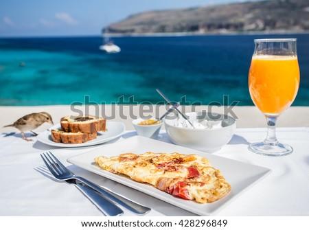 Greek breakfast with omelet and yogurt  against Mediterranean sea - stock photo