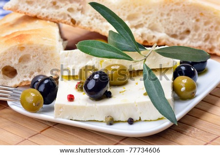 Greek cheese with green and black olives decorated by olive leaves - stock photo