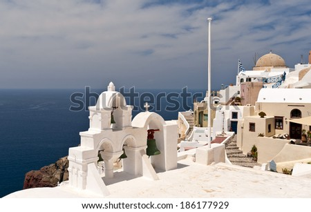 Greek church bell-tower and buildings over Aegean sea - stock photo