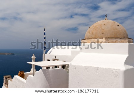 Greek church with bell-tower, national flags and sea view in spring day - stock photo
