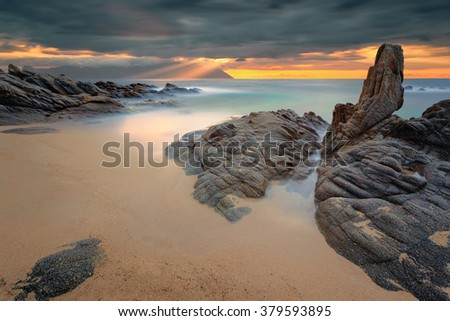 Greek coast of Aegean sea at dramatic morning with holy mountain Athos in clouds. Chalkidiki, Greece. Long exposure shot with beautiful sunbeams. - stock photo