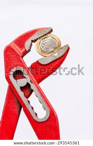 Greek Euro coin squezzed with pliers. Euro crisis. - stock photo