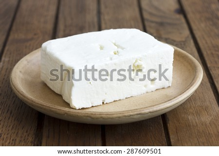Greek feta cheese block on rustic plate and table. - stock photo