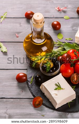 Greek feta cheese with fresh herbs, black and green olives, cherry tomatoes, selective focus