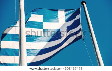 Greek flag in front of the EU Commission building in Brussels on blue clear sky - stock photo
