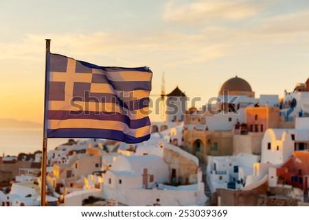 Greek flag waving at sunset in Oia, Santorini, Greece - stock photo