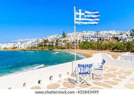 Greek flag waving on a terrace overlooking Piperi beach in Naossa village, Paros island, Cyclades, Greece - stock photo