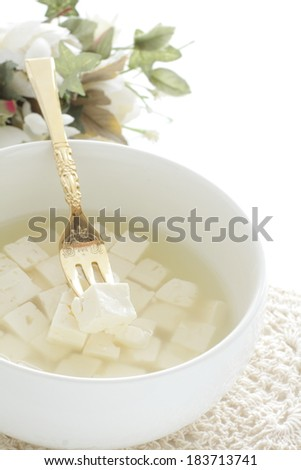 greek food, feta cheese in salted water with fork and flower on background