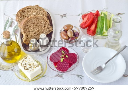 Greek food, mezedes. Jars with olive oil and vine vinegar,  olives,feta, tzatziki, dark bread, raki, beetroot, fresh cucumber and tomato on a white background. Healthy eating concept. Healthy food.