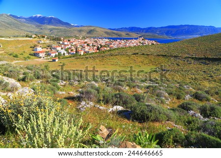 Greek hillside covered with green vegetation and distant village on the valley, Greece - stock photo