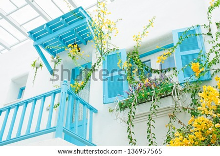Greek house style with blue window and rail fence in Santorini park - stock photo