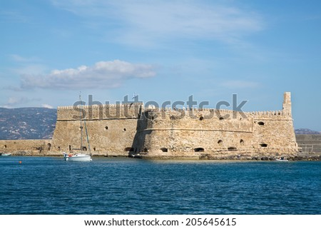 Greek island crete in the cyclades: sightseeing on the old port with fort and boats. - stock photo
