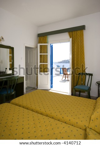 greek island hotel suite room with view of beach and cyclades architecture from hotel suite patio - stock photo
