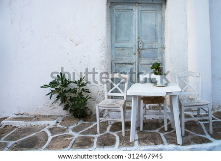Greek island restaurants with colorful tables and chairs. - stock photo