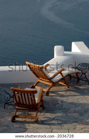 greek island santorini patio over the sea with lounge chairs - stock photo