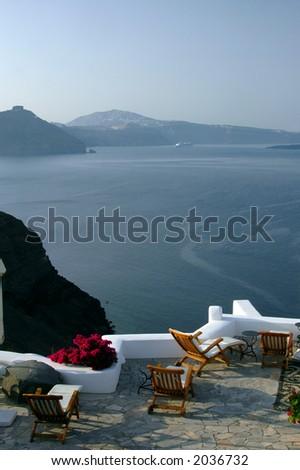 greek island santorini patio over the sea with lounge chairs - stock photo