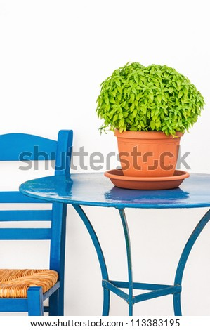 Greek island scene with blue chair, table and basil flowerpot - stock photo