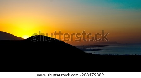 Greek Island Sunset - Sunset colors on the Malia Hersonissos harbor near Heraklion, Crete, Greece with the mountains touching the sea in silhuette - stock photo