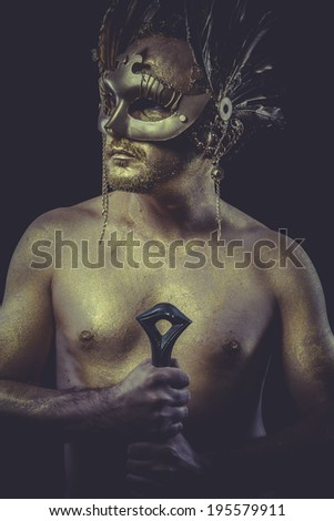 Greek man with body painted gold feather mask and steel sword - stock photo