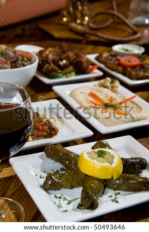 Greek mezze spread with roasted cauliflower, fried eggplant, lamb in vinegar, grape leaves, hummus, and fish over rice - stock photo