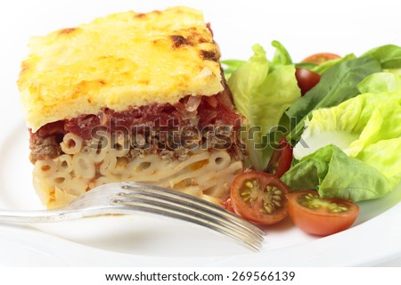 Greek pastitsio pasta topped with minced beef, tomatoes, bechamel sauce and cheese, served with a salad. - stock photo