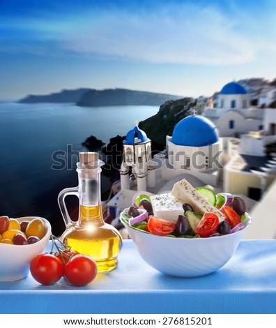 Greek salad against church in Oia village, Santorini island in Greece - stock photo
