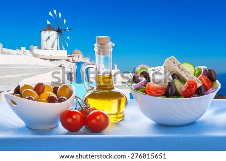 Greek salad against windmill in Oia village, Santorini island in Greece - stock photo