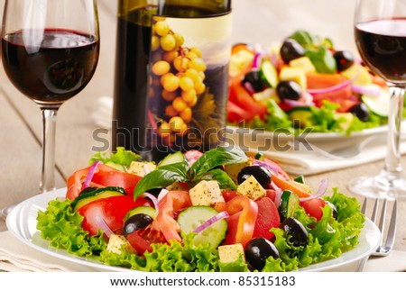 Greek salad and glass of red wine on the kitchen table - stock photo