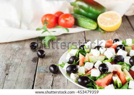 Greek salad and Ingredients in background. Closeup