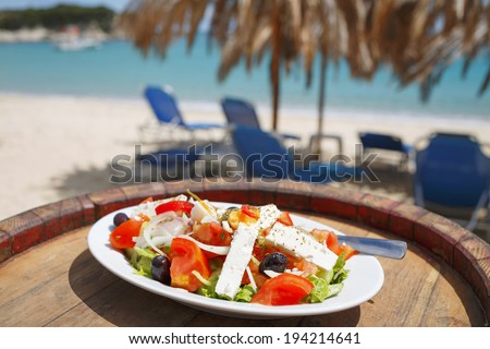 Greek salad/Fresh tasty vegetable salad with white feta cheese on wooden background. Restaurant on beach. - stock photo