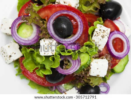 Greek salad in a plate on the table - stock photo