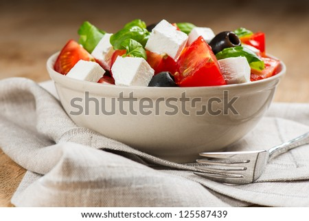 Greek salad in bowl on napkin - stock photo