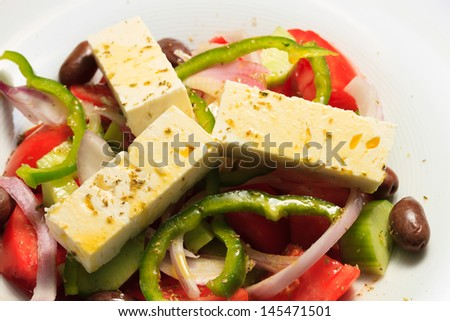 Greek salad, in closeup. Tomatoes, black olives, red onions, cucumber, rosemary and feta cheese.