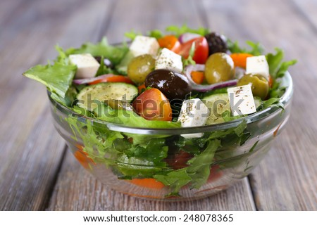 Greek salad in glass dish on wooden table background - stock photo