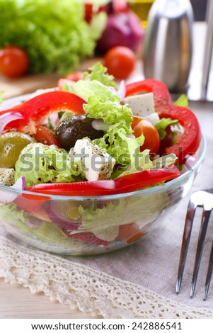 Greek salad in glass dish with fork and vegetables background - stock photo