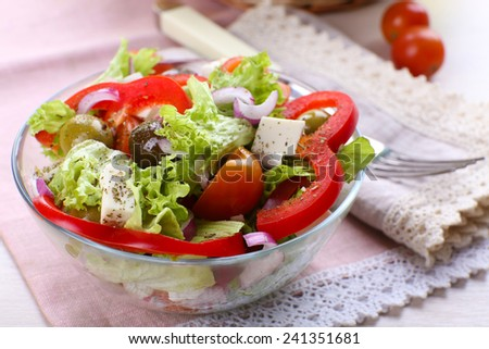Greek salad in glass dish with fork on napkin and wooden table background - stock photo