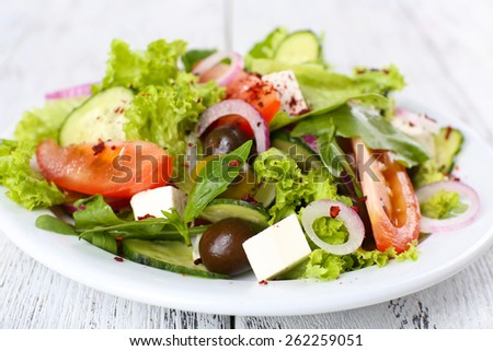 Greek salad in plate on color wooden table background - stock photo