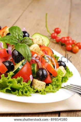 Greek salad in the white plate on the kitchen table - stock photo