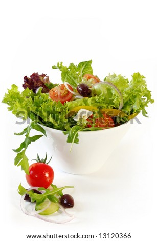 Greek salad in white bowl.  Mixed lettuce, red onion, cherry tomatoes, goat's cheese, black olives and capsicum.