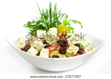 Greek Salad in white plate isolated on white - stock photo