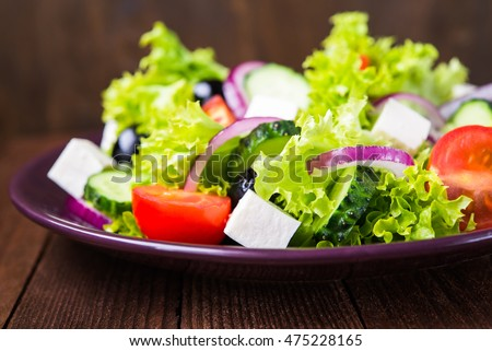 Greek salad (lettuce, tomatoes, feta cheese, cucumbers, black olives, purple onion) on dark wooden background close up. Healthy food.