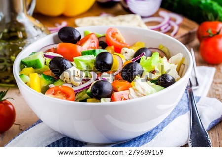 Greek salad of organic vegetables with tomatoes, cucumber, red onion, olives and feta cheese - stock photo
