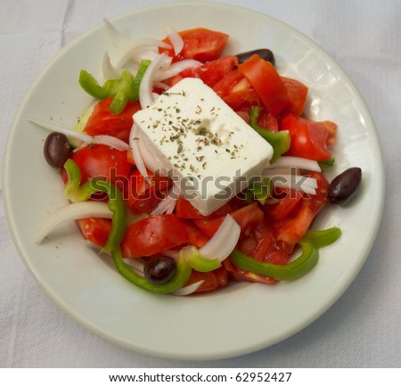 Greek salad on a plate with fresh veggies and feta cheese . - stock photo