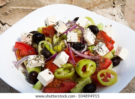 Greek salad on a white plate - stock photo