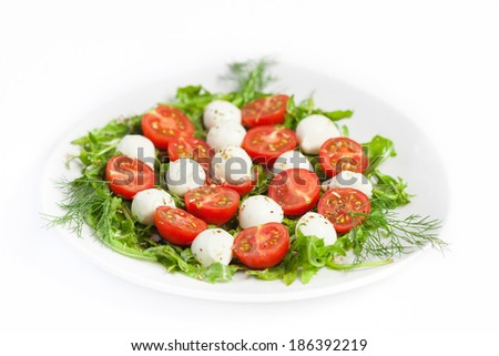 Greek salad on the plate, mozzarella cheese and cherry tomato, white background