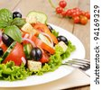 Greek salad on the white plate - stock photo