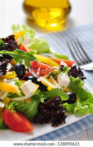 Greek salad on white plate on wooden background closeup
