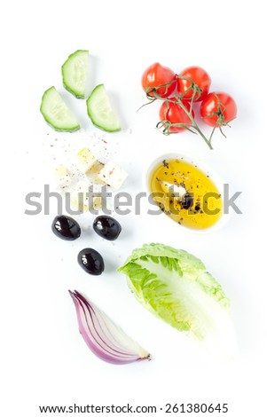 Greek salad recipe ingredients on white from above. Feta cheese, cherry tomatoes, onion, cucumber, olives, lettuce and olive oil.  - stock photo