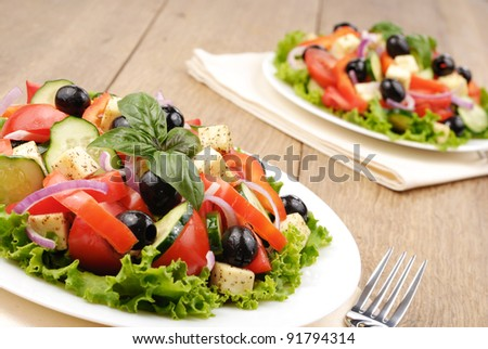 Greek salad served for two on the oak table
