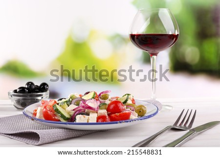 Greek salad served in plate with glass of wine on napkin on wooden table on natural background